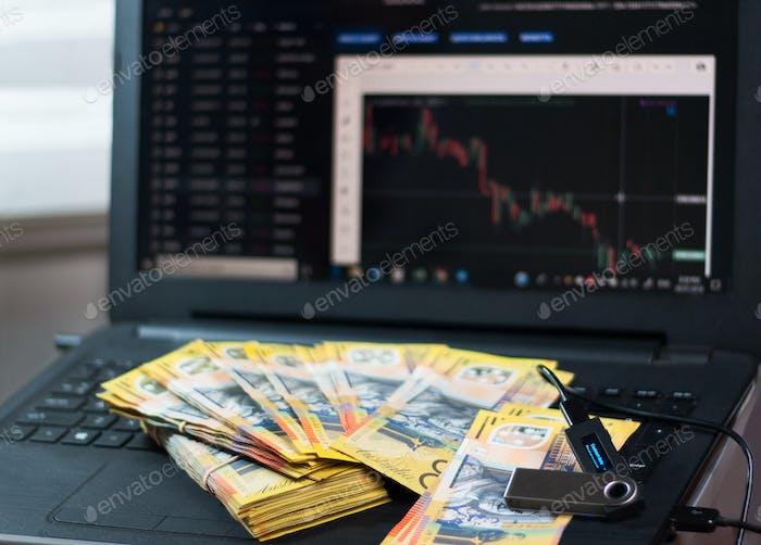 Australische Dollar und Nano-Geldbörse auf dem Laptop mit Grafiken und Diagrammen