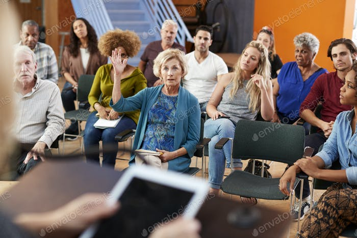 Woman Asking Question At Group Neighborhood Meeting In Community Center