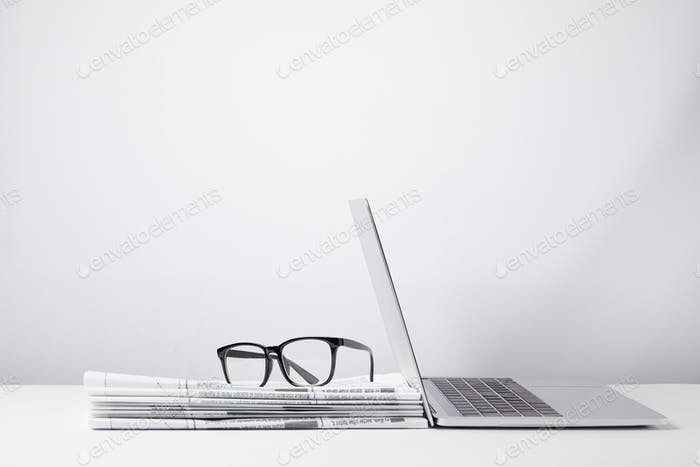 laptop and eyeglasses on heap of newspapers, on white