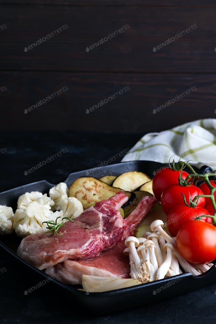 Raw lamb ribs marinating with fresh vegetables in a grill pan on a dark stone background