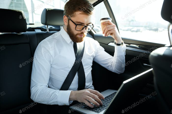 Concentrated business man using laptop and holding cup of coffee