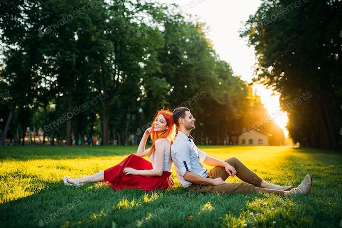 Liebespaar sitzt auf Gras im Park, romantisches Date