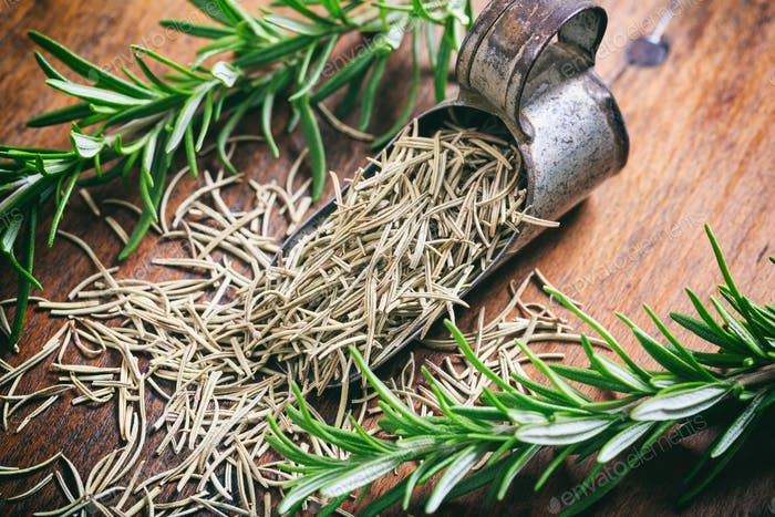 Fresh and dried rosemary on a wooden table