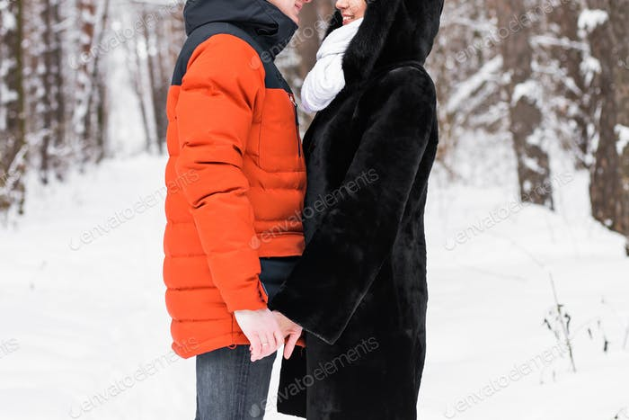 Young couple in love holding hands outdoor in winter
