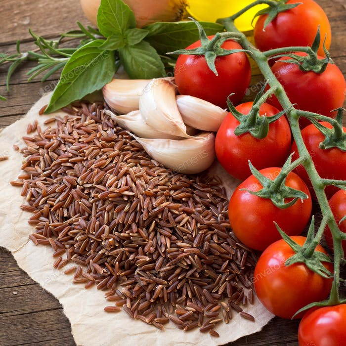 Red organic  rice, tomatoes, olive oil, garlic and herbs on wooden background
