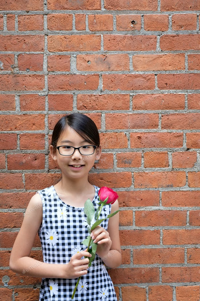 Portrait of young Asian girl with red rose flower against red brick wall