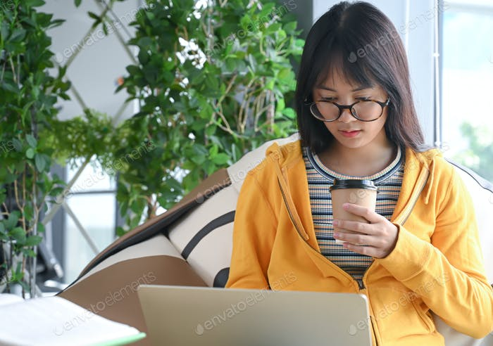 Asian female student wearing glasses is researching with a laptop to report.