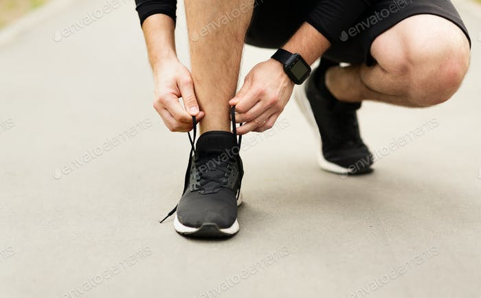 Man tying running shoes laces getting ready for run