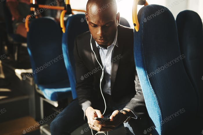 Businessman wearing earphones and reading text messages on a bus