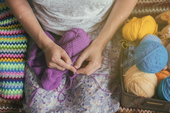 Caucasian woman knits woolen clothes. Holding knitting needles at hands