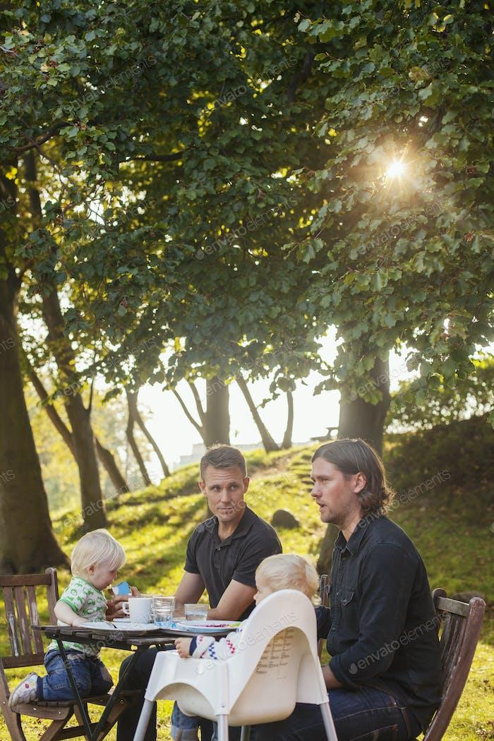 Väter und Kinder frühstücken am Tisch im Park
