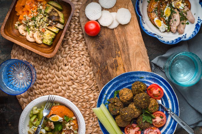 Falafel, salads with pumpkin, carrots, avocado on a wicker napkin