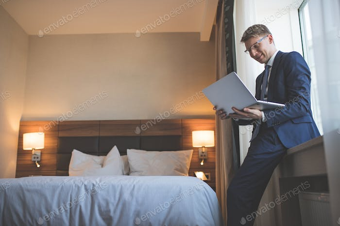 Smiling businessman with laptop in room