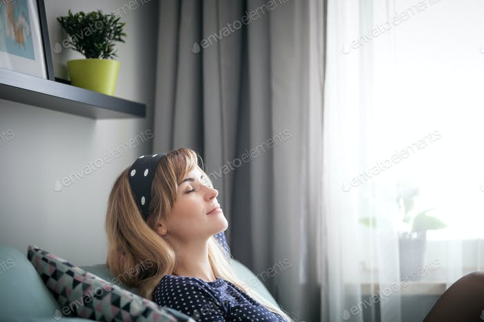 Happy young woman sitting on sofa relaxing at home, dreaming