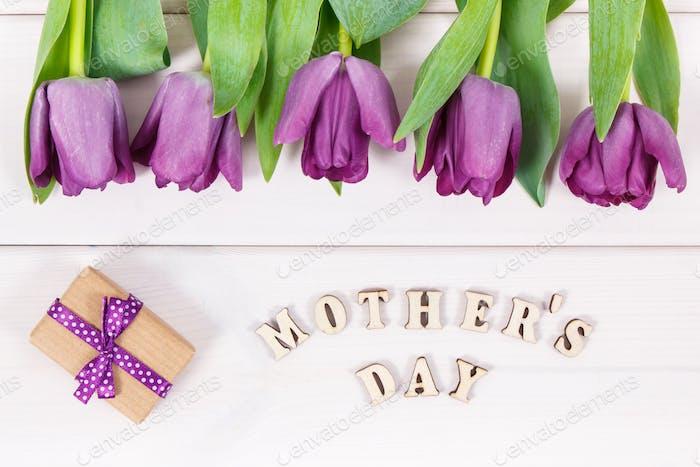 Blumenstrauß aus lila Tulpen und Geschenk für den Muttertag auf weißen Tafeln