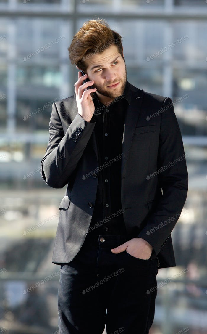 Handsome young man using mobile phone in the city