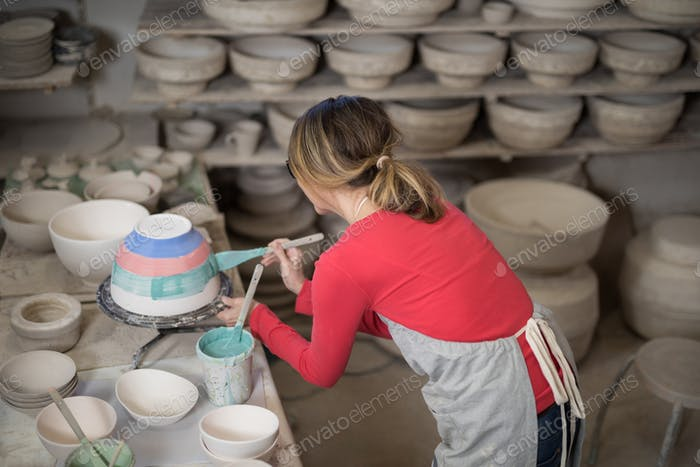 Female potter painting bowl