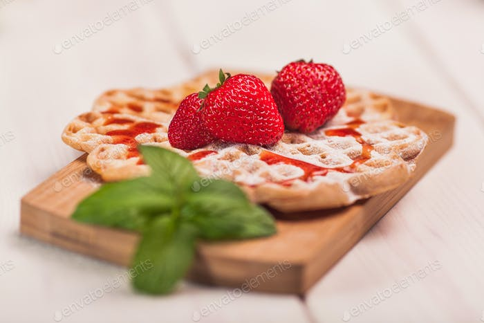 Waffles with strawberry on wooden plank