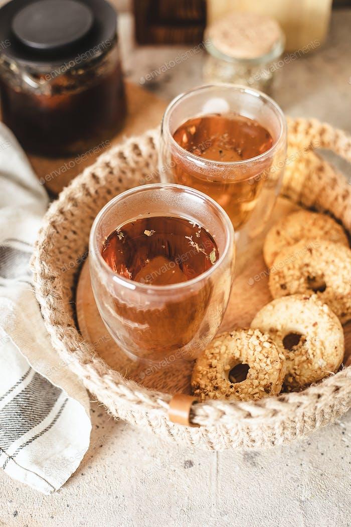 Glass of hot tea in jute basket in home interior. Breakfast food concept