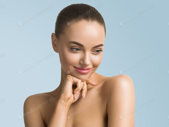 Clean skin woman face close up skin beauty tanned face beautiful smile over blue background