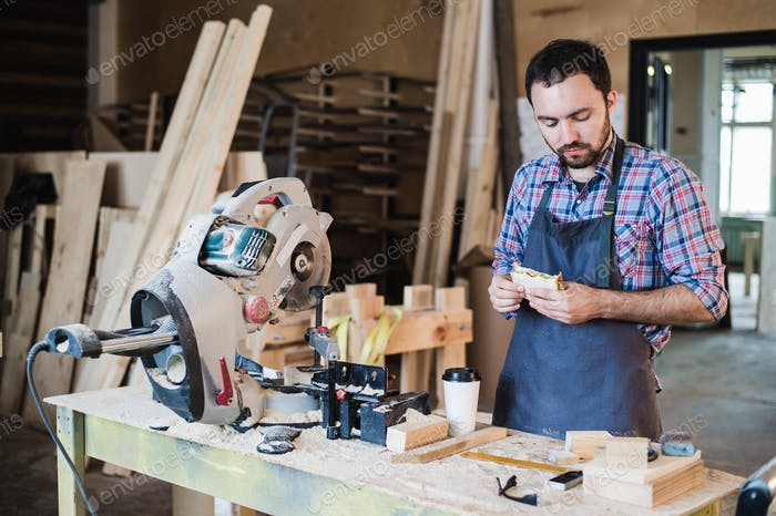 Cheerful carpentry worker having lunch eating sandwich in a workshop