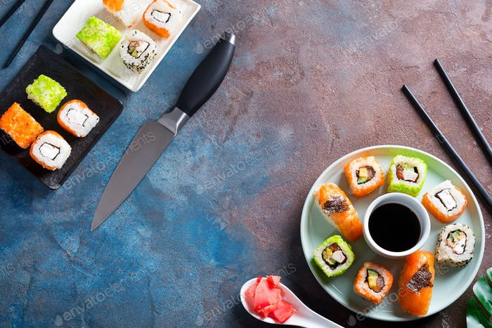 Freshly cooked sushi and rolls set with soy sauce on a ceramic plate with knife, metal chopsticks on