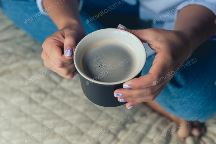 Cute girl with a beautiful manicure drinking coffee