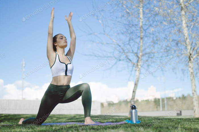 woman doing yoga and pilates outdoor with her mat