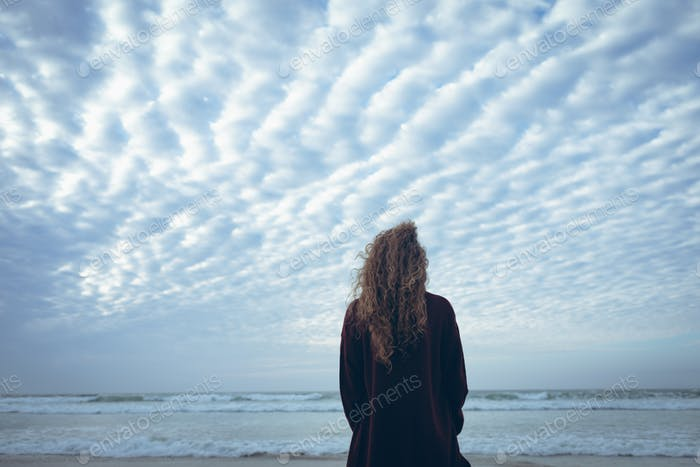 Beautiful young woman with curly hair standing and looking at the sea at beach