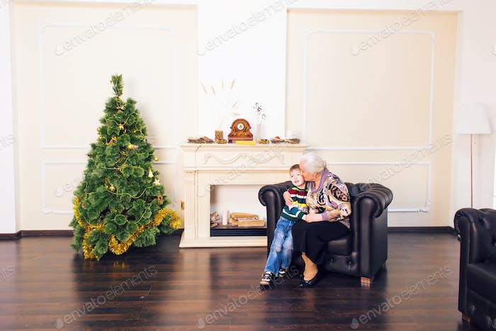 Grandchild and grandmother near the christmas tree