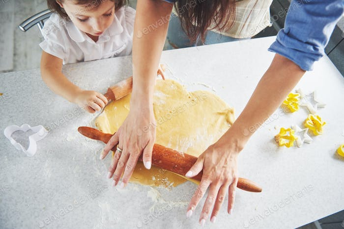 Family cooking Christmas cookies. Hands of mother and daughter preparing the dough on the table