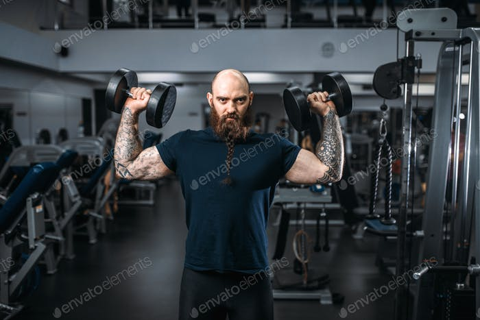 Muscular athlete poses with dumbbells in gym