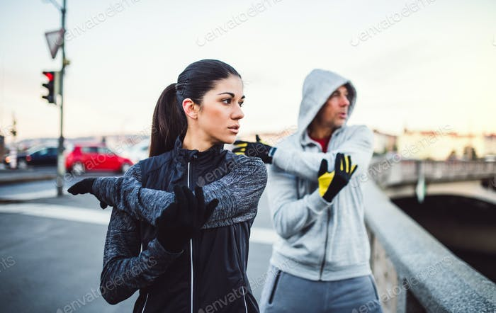 A fit couple runners doing stretching outdoors on the bridge in Prague city.