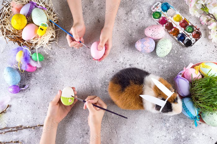 Preparing for Easter. Small children paint cookies and eggs with a guinea pig in the ears of a