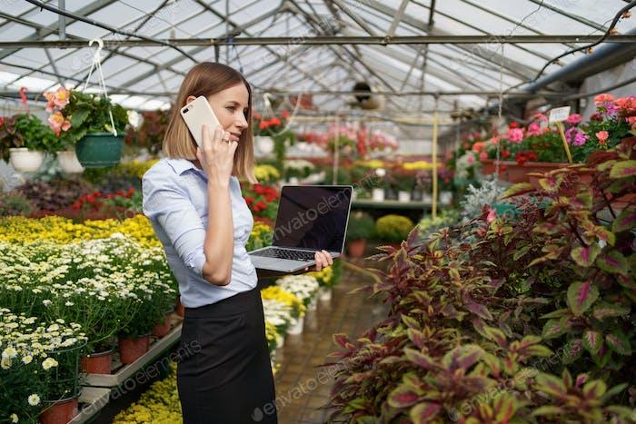 Woman entrepreneur portrait posing working in her greenhouse