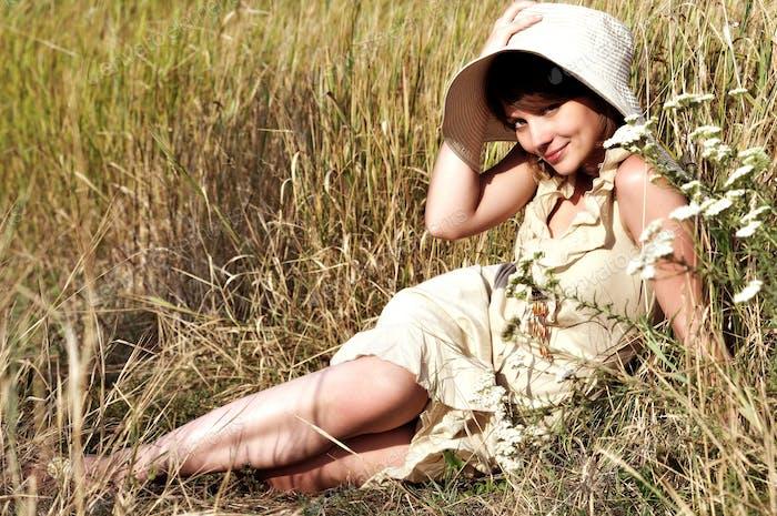 Woman lying on summer field among flowers