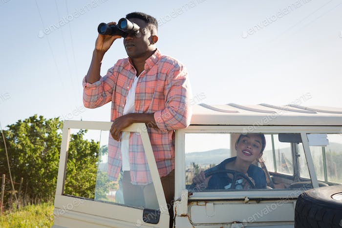 Man looking through binoculars at countryside