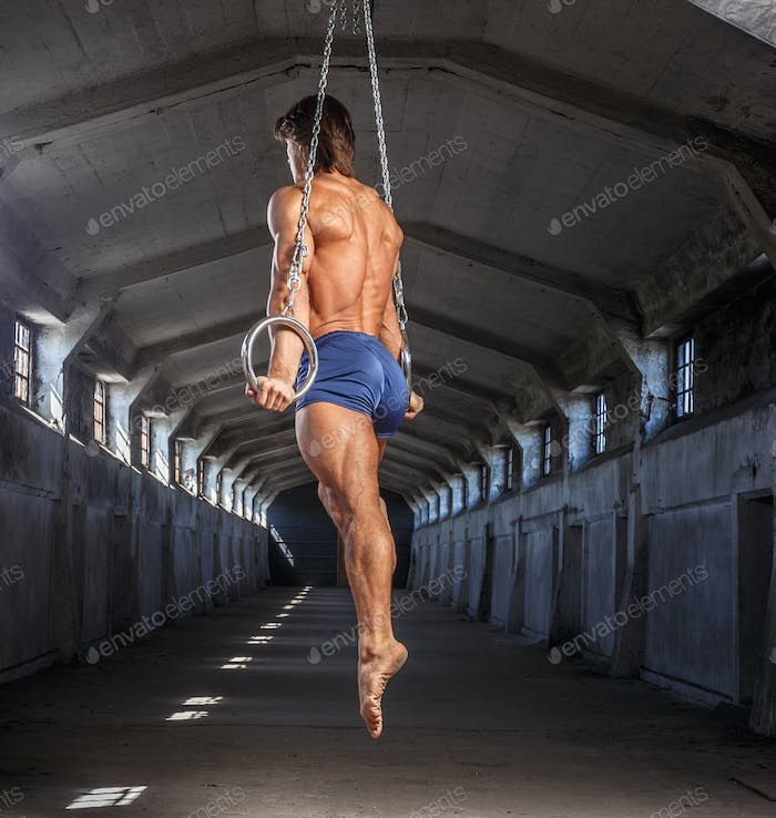 Man workouts with gymnastic rings.