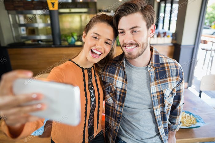 Cheerful friends taking selfie with mobile in restaurant
