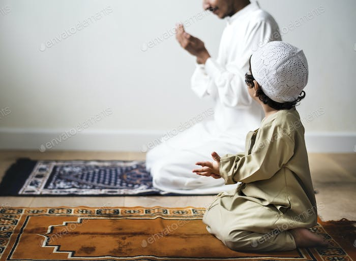 Little boy praying alongside his father during Ramadan