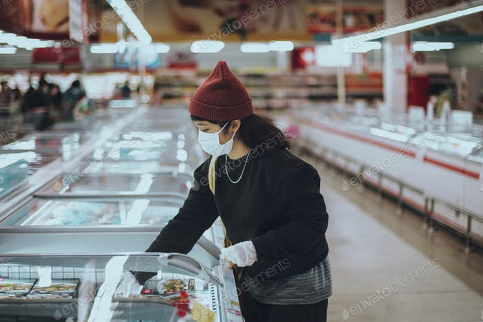 Woman with a medical mask buying frozen food during coronavirus pandemic