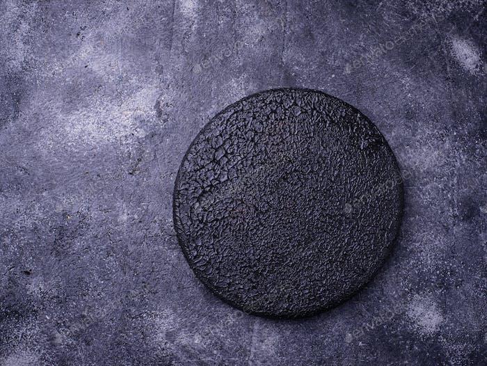 Empty black cutting board on concrete background