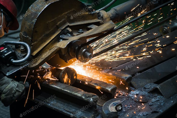 Sparks from circular saw at steel factory. Metal sawing close up