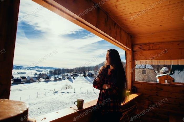 girl drinks tea on winter terrace