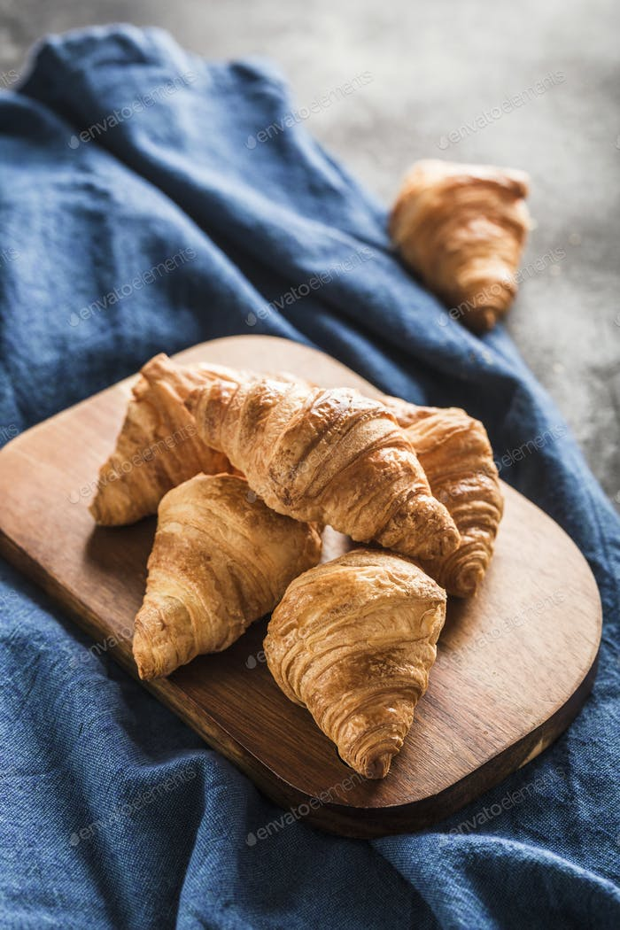 Freshly baked French croissants on a wooden Board on a light background with a blue napkin.