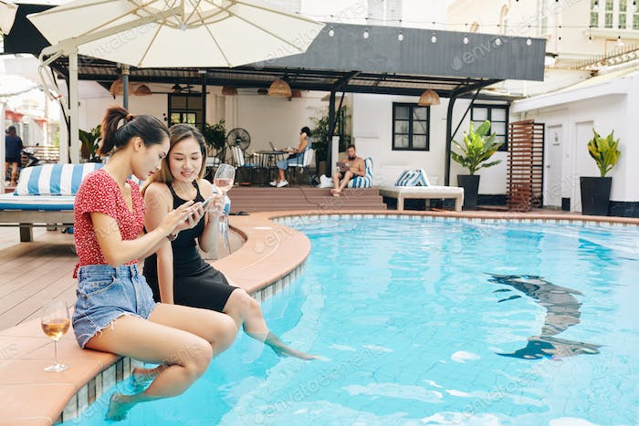 Female friends with smartphone sitting at pool