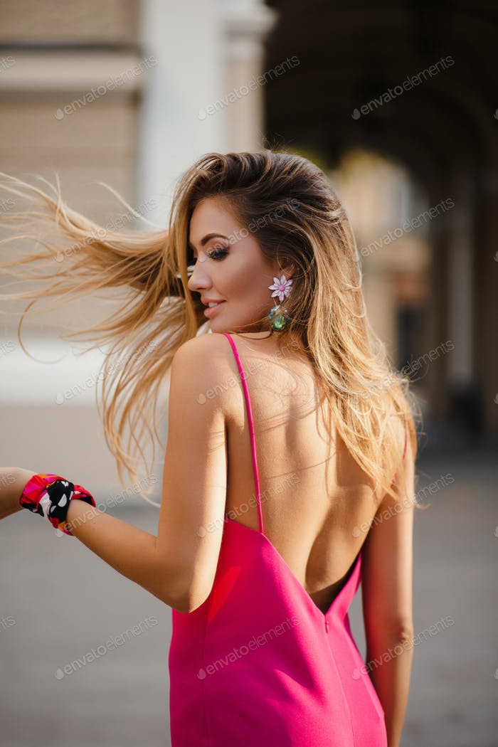elegant attractive woman wearing pink sexy summer dress walking in street