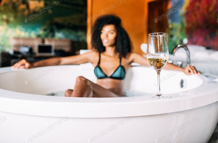 Wine glass with woman relaxing in the hydro massage bath