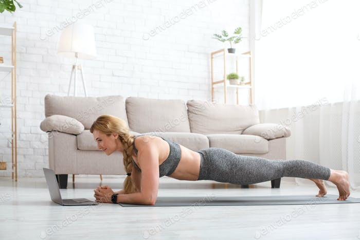 Sport and work online. Woman in sportswear makes plank and looks at laptop on floor