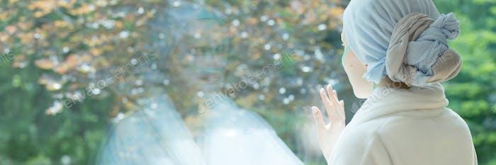 Panorama der kranken Frau mit Krebs berühren Fenster im Hospic